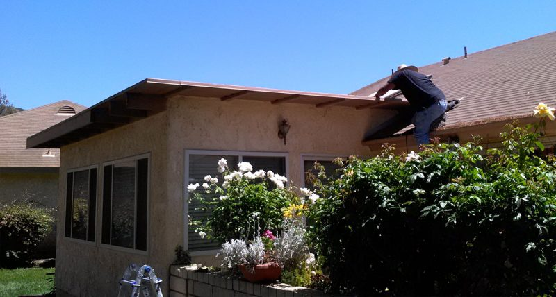 A worker removes rotted, termite-infested fascia boards in Ventura County
